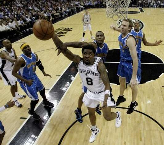 The Spurs' Roger Mason Jr. drives to the basket under pressure from the Hornets' Rasual Butler (center left) and Sean Marks at the AT&T Center on Wednesday, April 15, 2009. The Spurs won 105-98 in overtime. (Jerry Lara / San Antonio Express-News)