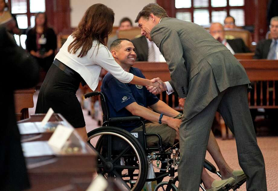 Texas Gov. Rick Perry Perry presents the award to Jonathan Esquivel, who was injured with the San Antonio Police Department as he is wheeled in by his wife after Perry gave remarks where he presented the 2012 Star of Texas Awards, which honor peace officers. firefighters, emergency medical first responders and federal law enforcement agents that have been seriously injured or killed inn the line of duty, during a ceremony in the House Chambers in Austin, Texas, Friday morning, Sept. 14, 2012. (AP Photo/Statesman.com, Ralph Barrera)  MAGS OUT; NO SALES; INTERNET AND TV MUST CREDIT PHOTOGRAPHER AND STATESMAN.COM Photo: Ralph Barrera, Associated Press / American-Statesman