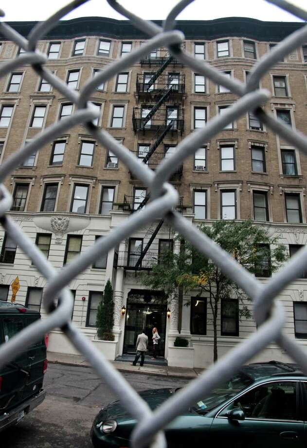 A building serving as an adult  shelter of 95th Street is viewed from behind the fenced playground P.S. 75 on Friday, Sept. 28, 2012 in New York.  Neighborhood residents are in turmoil, saying they were blindsided by the suddenness of the shelter's opening, sharing the same block as the school.   (AP Photo/Bebeto Matthews) Photo: Bebeto Matthews
