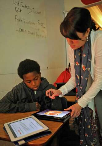 Sixth grade math teacher Staci Davis, right, uses her iPad to help Harold Mitchell, left, get through one of the problems the class was working on.  Every student is using one as she goes through a math problem on hers which projects onto the screen as well. Henderson Middle School in Sour Lake Texas are allowing their sixth grade students to take home iPads that they use in the classroom as well as do homework on.   Dave Ryan/The Enterprise