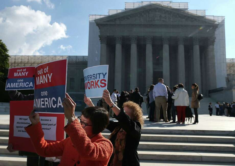 WASHINGTON, DC - OCTOBER 10: Protesters hold signs in front of the U.S. Supreme Court on October 10, 2012 in Washington, DC. The high court is scheduled to hear arguments on Fisher V. University of Texas at Austin and are tasked with ruling on whether the university's consideration of race in admissions is constitutional. Photo: Mark Wilson, Getty Images / 2012 Getty Images