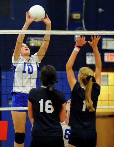 Darien's #10 Taylor Cockerill, left, tries to send the ball over Staples players #16 Jennifer Dimitrief, center, and #11 Claire Naughton, during girls volleyball action in Westport,Conn. on Tuesday October 9, 2012. Photo: Christian Abraham / Connecticut Post