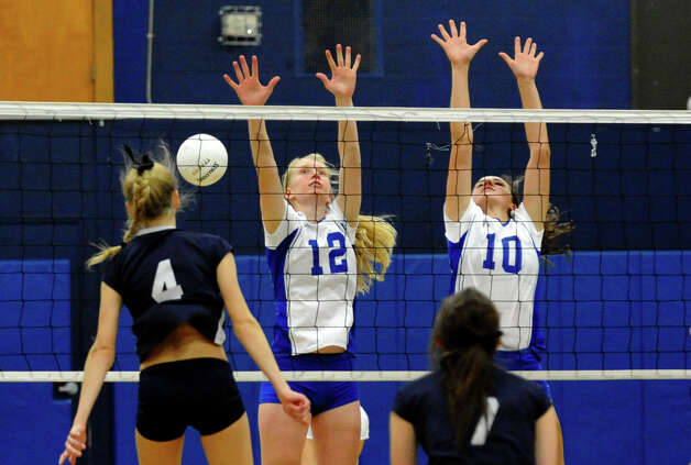 Darien's #12 Celia Martzoff, center, and #10 Taylor Cockerill fail to stop a shot by Staples #4 Amelia Brackett, left, during girls volleyball action in Westport, Conn. on Tuesday October 9, 2012. Photo: Christian Abraham / Connecticut Post