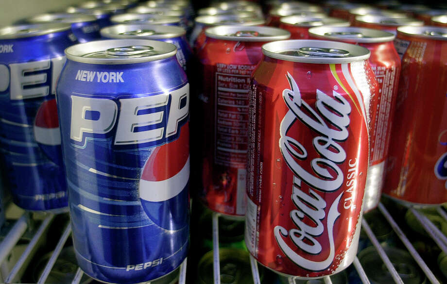 Cans of Pepsi and Coke are shown in a news stand refrigerator display rack in New York Friday, April 22, 2005. (AP Photo/Mark Lennihan) Photo: MARK LENNIHAN, STF / AP2005