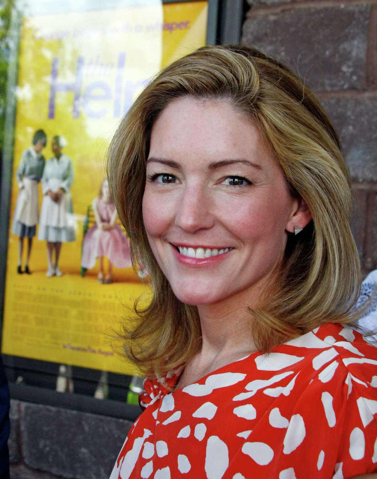Author Kathryn Stockett poses by a poster for the movie made from her book prior to a benefit screening of