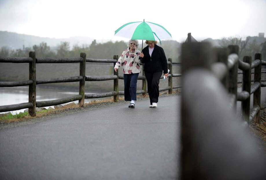"Charlene Circio, of Stratford, left, and Carol Pluchino, of Ansonia, take their daily walk, ""rain or shine,"" Wednesday, Oct. 10, 2012 at the Derby Riverwalk. Photo: Autumn Driscoll / Connecticut Post"