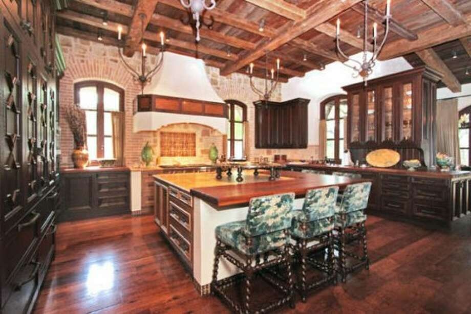 The kitchen is rustically luxurious with its ceiling of heavy wood beams, hanging fixtures and dark-stained ornate cabinetry by Palmer Todd.