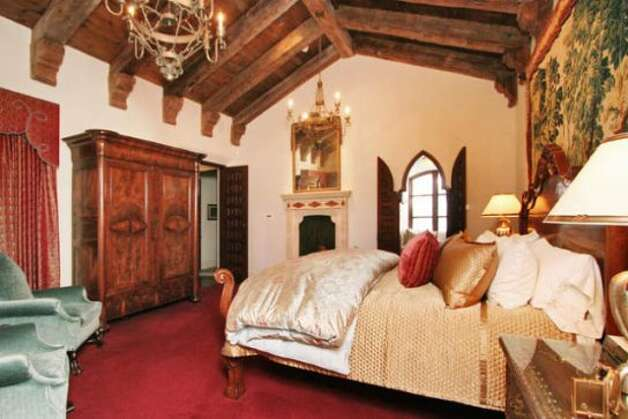 The bedroom has high-vaulted ceilings, a fireplace and mahogany doors with decorative inlays.