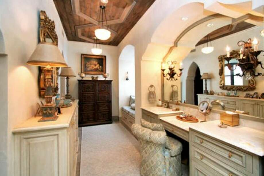 A powder room fit for a queen: the large mirror is sculpted to the shape of the inset wall above the vanity. There is also a window-lit sitting area.