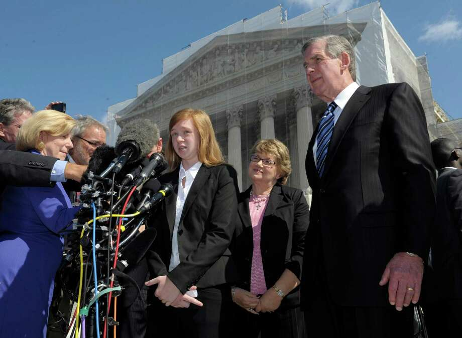 Abigail Fisher, the Texan involved in the University of Texas affirmative action case, accompanied by her attorney Bert Rein, right, talks to reporters outside the Supreme Court in Washington, Wednesday, Oct. 10, 2012. The Supreme Court is taking up a challenge to a University of Texas program that considers race in some college admissions. The case could produce new limits on affirmative action at universities, or roll it back entirely. The University of Texas at Austin President Bill Powers is at right.(AP Photo/Susan Walsh) Photo: Susan Walsh, Associated Press / AP