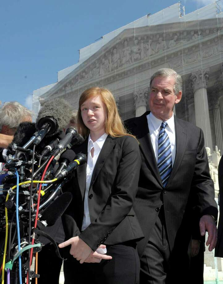 Abigail Fisher, the Texan involved in the University of Texas affirmative action case, accompanied by her attorney Bert Rein, talks to reporters outside the Supreme Court in Washington, Wednesday, Oct. 10, 2012. The Supreme Court is taking up a challenge to a University of Texas program that considers race in some college admissions. The case could produce new limits on affirmative action at universities, or roll it back entirely. The University of Texas at Austin President Bill Powers is at right. (AP Photo/Susan Walsh) Photo: Susan Walsh, Associated Press / AP