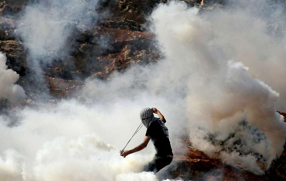 A masked Palestinian protester hurls back a tear gas canister shot by Israeli soldiers, unseen, during clashes outside the Ofer military prison, near the West Bank city of Ramallah, Wednesday, Oct. 10, 2012. The clashes started during a demonstration calling to release prisoners jailed in Israel. Photo: Majdi Mohammed, Associated Press