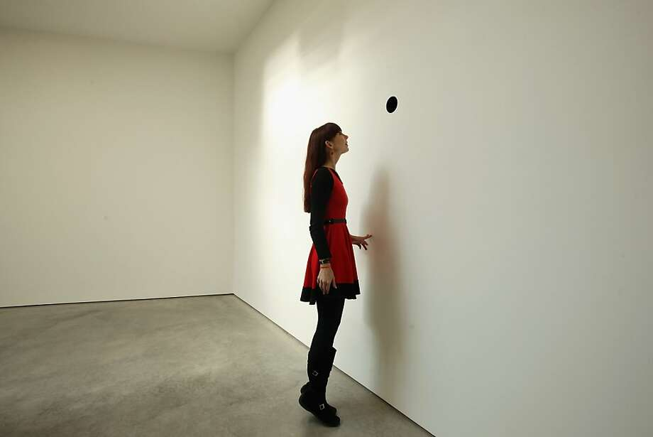 If you look inside, you can see the artist snickering: A journalist examines a work by artist Anish Kapoor consisting of a small black hole in a wall during a preview of his new exhibition at the Lisson Gallery in London. Photo: Dan Kitwood, Getty Images