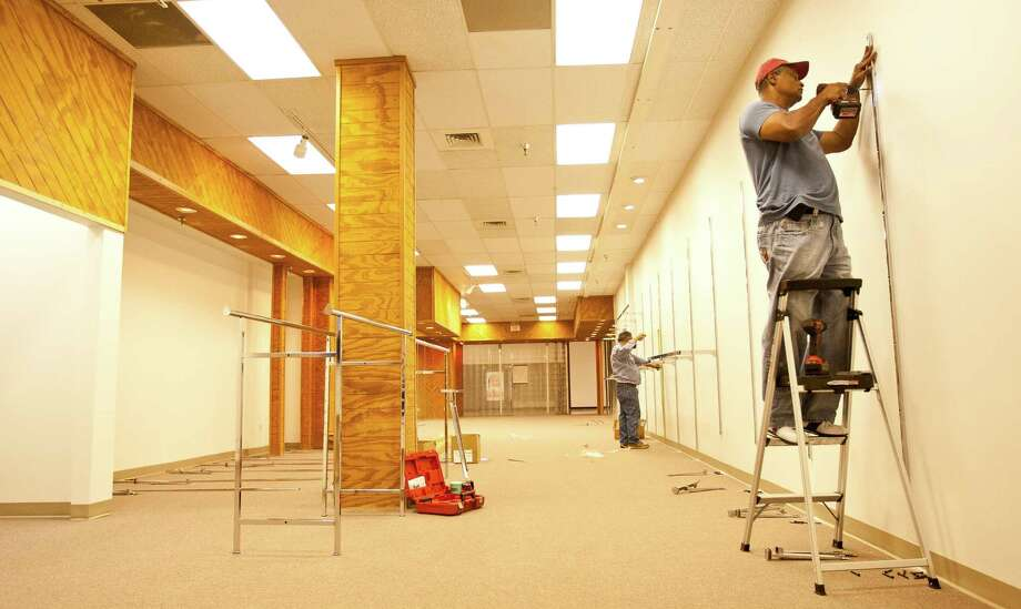 Steven Cook, The Men's Warehouses' Vice President of Community Relations, front installs clothing pipes along the walls of Career Gear's new location, Tuesday, Sept. 25, 2012, in the Plaza de Americas mall in Houston. Career gear is a nonprofit place for men to get a free business suit for job interviews. The agency received a $10,000 check from a couple from The Woodlands to help relocate. ( Nick de la Torre / Houston Chronicle ) Photo: Nick De La Torre / © 2012 Houston Chronicle
