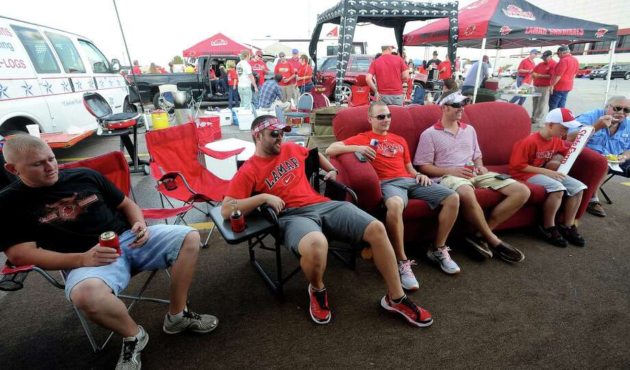 Lamar fans hang out on a couch watching football while tailgating before the homecoming game against