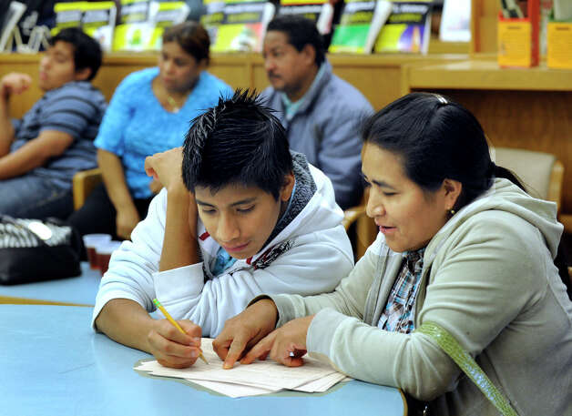 Jose Morquecho, 14, left, and his mother, Maria, fill out a form together at an informational meeting for parents of English language learners at Danbury High School, Tuesday, Oct. 9, 2012. Photo: Carol Kaliff / The News-Times