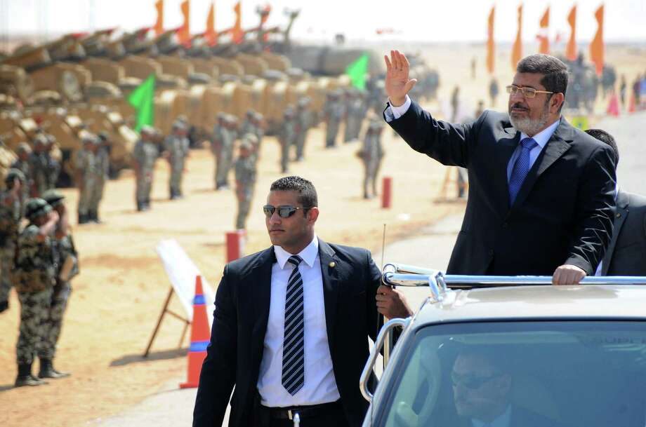 Egyptian President Mohammed Morsi reviews troops. A new Mideast is rising, but,  paradoxically, the same social, religious and political woes remain.