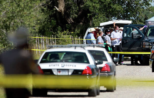 Officials investigate a scene in Atascosa County where former County Commissioner Tommy Shearrer was killed. Photo: Tom Reel, San Antonio Express-News / ©2012 San Antono Express-News