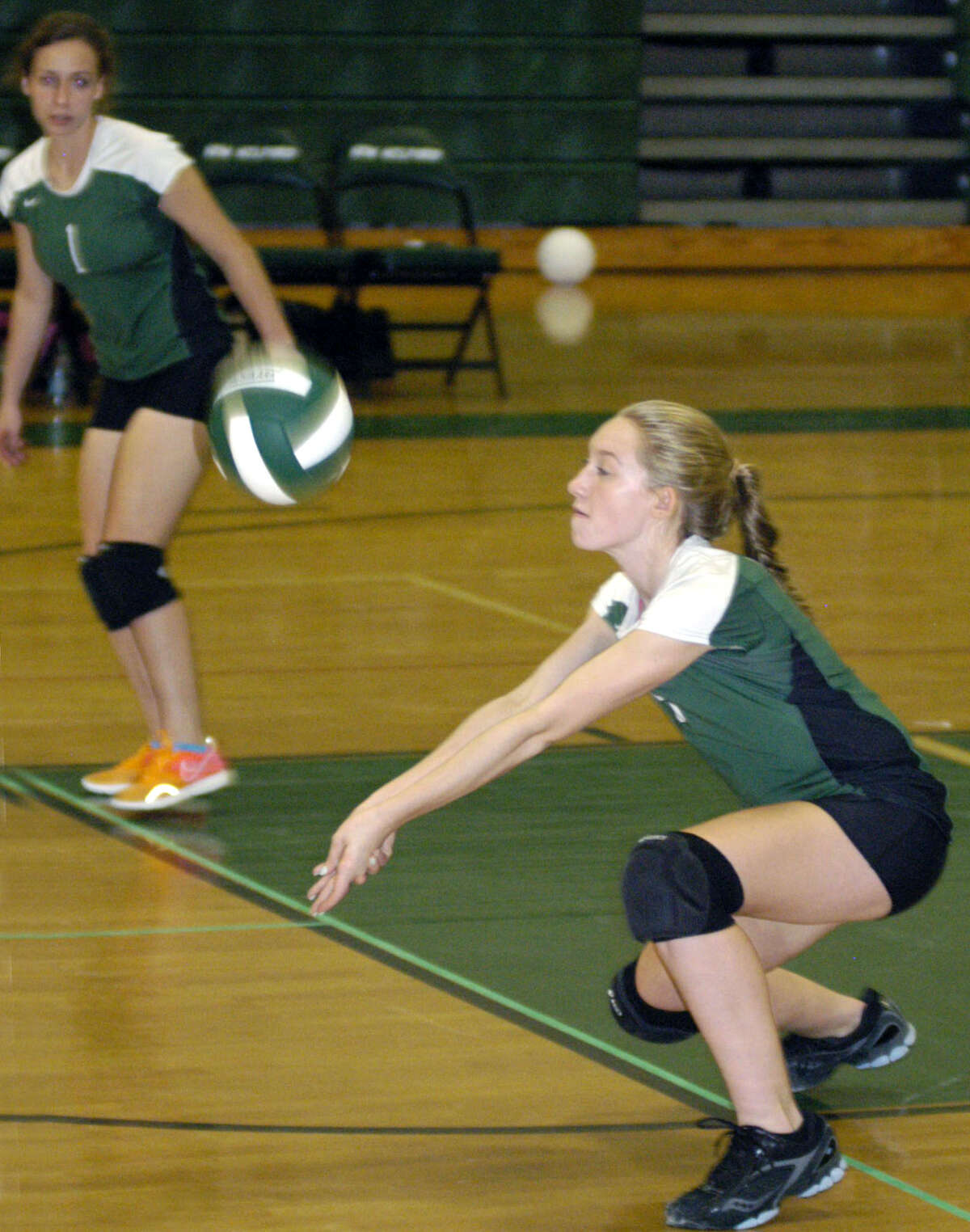 The Green Wave's Stephanie Fleet digs one out as teammate Juliana Fusco looks on during New Milford High School volleyball's victory over visiting Notre Dame of Fairfield, Oct. 5, 2012
