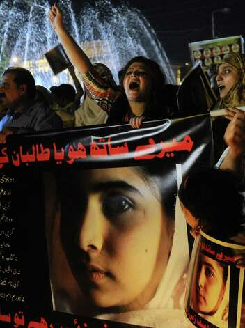 Pakistani civil society activists carry placards with photographs of gunshot victim Malala Yousafzai and shot slogans during a protest rally against her assassination attempt, in Lahore on October 10, 2012. Pakistani doctors removed a bullet from a 14-year-old child campaigner shot by the Taliban in a horrific attack condemned by national leaders and rights activists. The attack took place in Mingora, the main town of the Swat valley in Pakistan's northwest, where Malala had campaigned for the right to an education during a two-year Taliban insurgency which the army said it had crushed in 2009. AFP PHOTO/ Arif AliArif Ali/AFP/GettyImages Photo: ARIF ALI, AFP/Getty Images / AFP