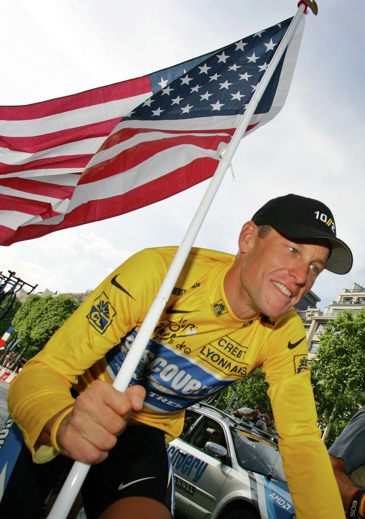 In 2005, Armstrong carried the U.S. flag during a victory parade on the Champs Elysees after winning his seventh straight Tour de France.