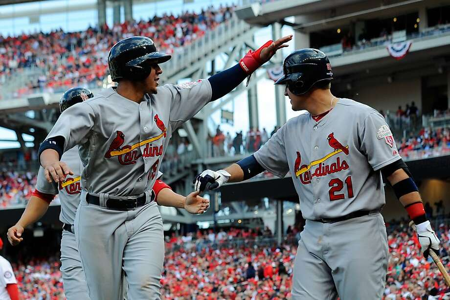 Allen Craig (right) greets Jon Jay (front left) and Carlos Beltran after they scored in the eighth. Photo: Patrick McDermott, Getty Images
