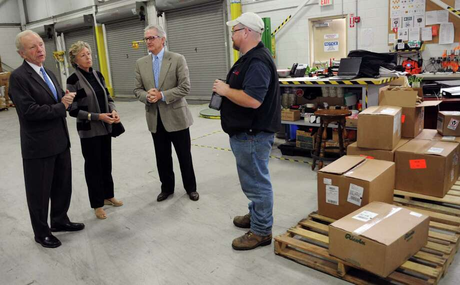 Senator Joseph Lieberman, left, and his wife, Hadassah, speak to Dennis Brown, far right, during a tour of AmeriCares from President and CEO Curt Welling in Stamford on Wednesday, October 10, 2012. Photo: Lindsay Niegelberg / Stamford Advocate