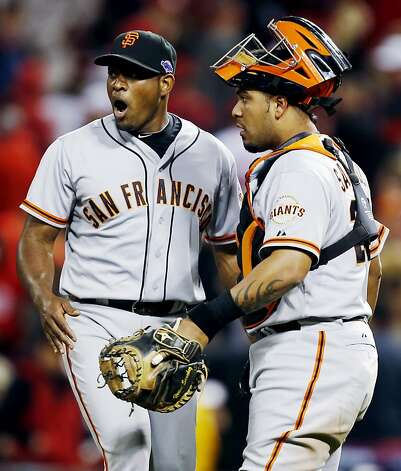 San Francisco Giants relief pitcher Santiago Casilla, left, is congratulated by catcher Hector Sanchez after the Giants defeated the Cincinnati Reds 8-3 in Game 4 of the National League division baseball series, Wednesday, Oct. 10, 2012, in Cincinnati. (AP Photo/David Kohl) Photo: David Kohl, Associated Press