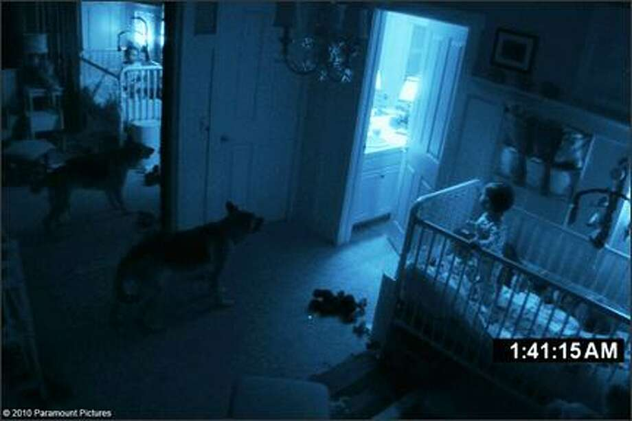 """10. """"Paranormal Activity""""(2007):  This low-budget movie about a haunted house that terrorizes a couple makes good use of its bland, suburban setting. Suspense is carefully squeezed out, and the fake-real video footage format heightens the fear. Photo is from """"Paranormal Activity 2."""" Photo: Paramount Pictures"""