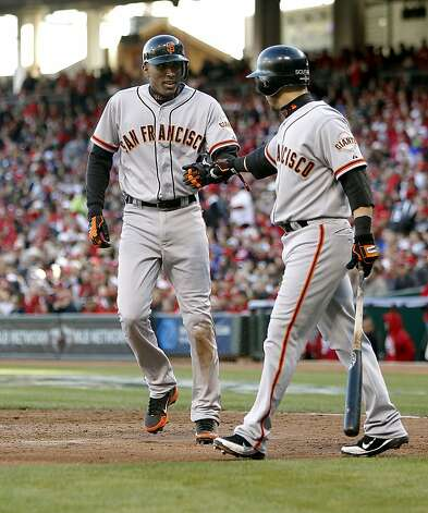 Giants' Joaquin Arias, (left) with Marco SAcutaro, scores in the fifth inning on a Angel Pagan double to make it 5-2,  as the San Francisco Giants went on to beat the Cincinnati Reds 8-3 to take game four of the National League Division Series in Cincinnati, Ohio on Wednesday Oct. 10, 2012. Photo: Michael Macor, The Chronicle