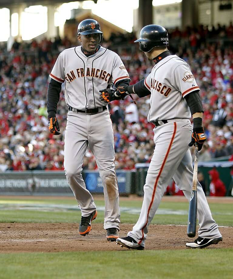 Joaquin Arias (left), greeted by Marco Scutaro, scores on Angel Pagan's fifth-inning double that made it 5-2 Giants. Photo: Michael Macor, The Chronicle