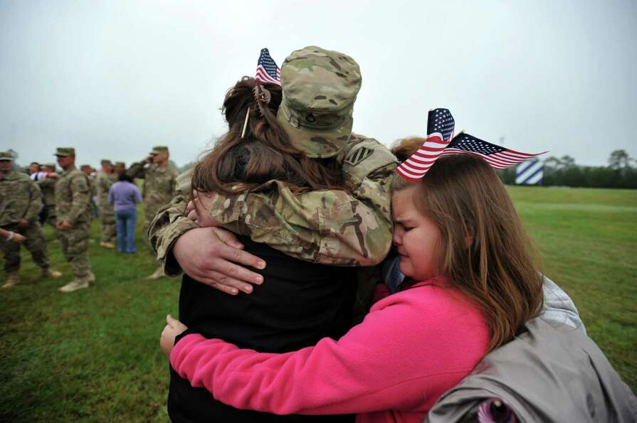 Army Pfc. Derek Southard, center, is hugged by his mother Shawn Southard, left, and his sister Jayle