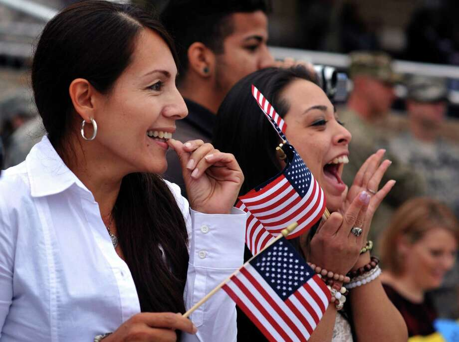 Patricia Parra, left, spots her son PFC Fabian Castrillon in formation along with his fiancee Marivel Penalea, right, during a welcome home ceremony for soldiers from the Army's 1st Battalion, 30th Infantry Regiment, Wednesday, Oct. 10, 2012 at Fort Stewart, Ga. One hundred troops returned home after their first deployment to Afghanistan. Overall about 2,200 soldiers from Fort Stewart's 3rd Infantry Division have deployed to Afghanistan this year. (AP Photo/Stephen Morton) Photo: Stephen Morton, Associated Press / FR56856 AP