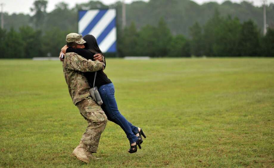 Army PFC Fabian Castrillon hugs his fiancee Marivel Penalea, right, during a welcome home ceremony for 100 soldiers from the Army's 1st Battalion, 30th Infantry Regiment, Wednesday, Oct. 10, 2012 at Fort Stewart, Ga. Overall about 2,200 soldiers from Fort Stewart's 3rd Infantry Division have deployed to Afghanistan this year. (AP Photo/Stephen Morton) Photo: Stephen Morton, Associated Press / FR56856 AP