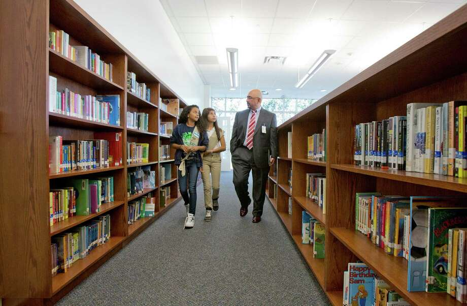 10/1/12: From left to right, Grady Middle School students, seventh grader Shinelle Baretto, age 12 and six grader Dennysse Castillo, age 11 give Michael Cardona, HISD Chief Middle School Officer at tour of the new library located in the new addition oat Grady Middle School in Houston, Texas. The addition was built under the district's 2007 capital program. The school would be completed under the 2012 bond proposal. Photo: Thomas B. Shea / © 2012 Thomas B. Shea