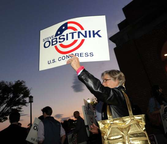 Kathy LoCurto of Westport holds up a Steve Obsitnik for U.S. Congress sign prior to the World Affairs Forum debate between Steve Obsitnik, the Republican challenger, and incumbent U.S. Rep. Jim Himes, D-Conn., 4th District, at Hyatt Regency Greenwich, Wednesday night, Oct. 10, 2012. Photo: Bob Luckey / Greenwich Time