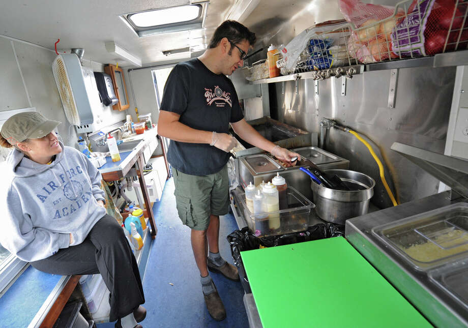 Andrea Loguidice and her boyfriend Brandon Snooks, both of Schenectady, work on the Wandering Dago food truck outside Schenectady County Public Library Tuesday, Oct. 9, 2012 in Schenectady, N.Y. (Lori Van Buren / Times Union) Photo: Lori Van Buren