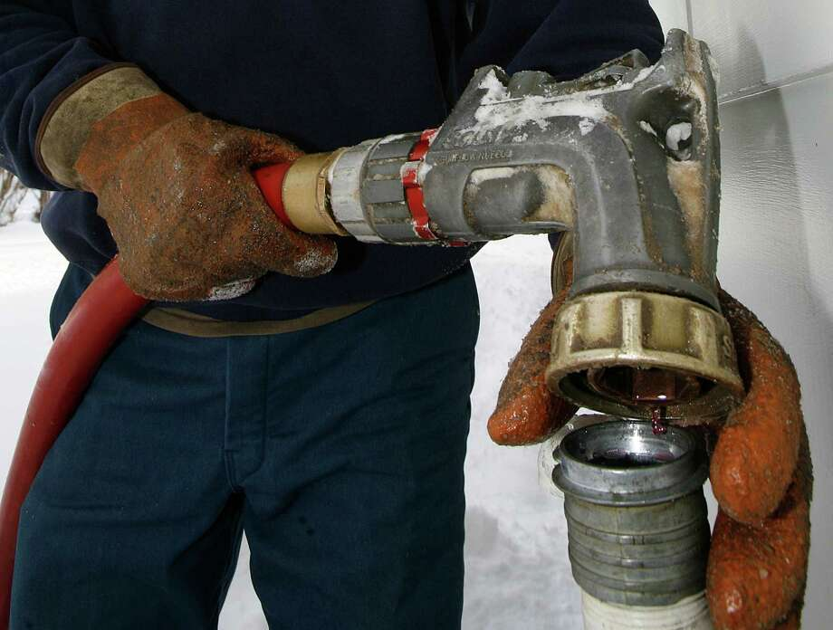 FILE - In this Jan. 2, 2008, file photo, Wayne Holland of the Suburban Propane company delivers oil in Barre, Vt.  Americans will pay more to heat their homes during the 2012-2013 winter season as they feel something they didn't feel much of last year: cold. Fuel prices will be relatively stable, but customers will have to use more energy to keep warm than they did a year ago, according to the annual Winter Fuels Outlook from the Energy Department's Energy Information Administration. (AP Photo/Toby Talbot, File) Photo: Toby Talbot