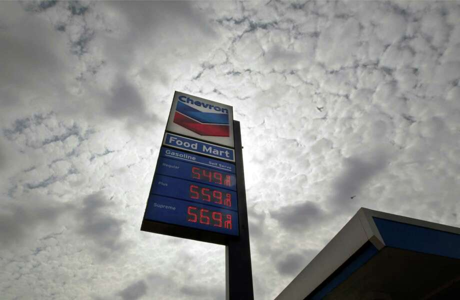 """FILE - In this Tuesday, Oct.  9, 2012, file photo, a Chevron station posts gasoline prices starting at $5.50 per gallon in downtown Los Angeles. Shares of Chevron Corp. plunged Wednesday after the oil giant said its third-quarter earnings are expected to be """"substantially lower"""" than in the second quarter. (AP Photo/Reed Saxon, File) Photo: Reed Saxon"""