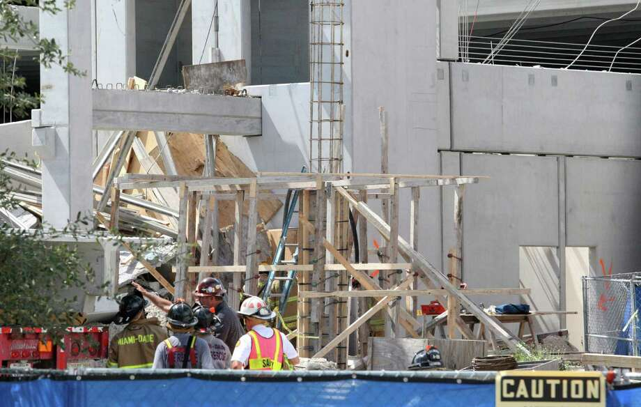 Miami-Dade Fire-Rescue workers view the West Campus parking lot of the Miami-Dade College in Doral, Fla., on Wednesday, Oct. 10, 2012. A section of the parking garage under construction collapsed Wednesday, trapping some workers and shaking the buildings around it. (AP Photo/El Nuevo Herald, Hector Gabino)  MAGS OUT Photo: Hector Gabino