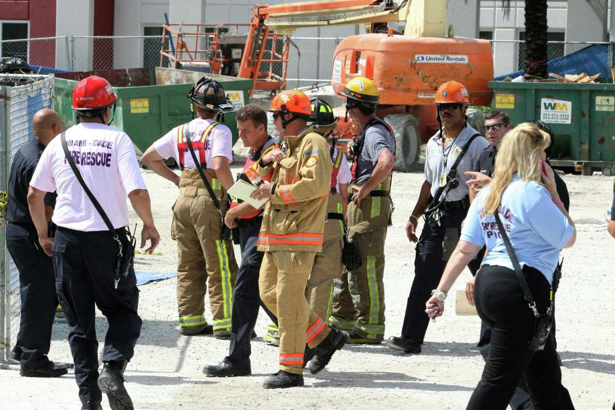 Miami Dade Fire Rescue workers wait at the scene of a parking garage collapse at the Miami-Dade College in Doral, Fla., on Wednesday, Oct. 10, 2012. A section of the parking garage under construction collapsed Wednesday, trapping some workers and shaking the buildings around it. (AP Photo/El Nuevo Herald, Hector Gabino) MAGS OUT