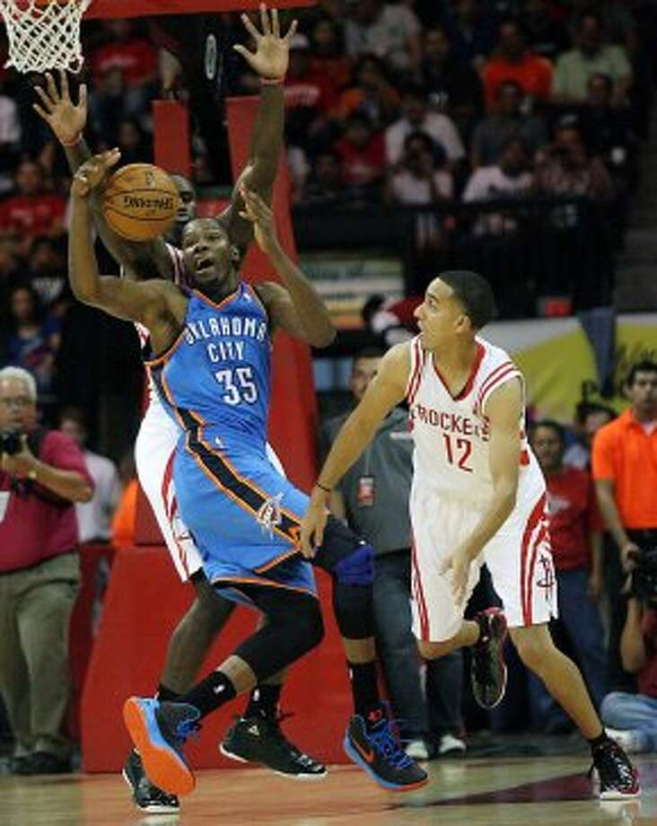 Oklahoma City Thunder's Kevin Durant (35) gets stripped of the ball by Houston Rockets' Patrick Patterson and Jeremy Lamb, right, during the first quarter of an NBA preseason basketball game in Hidalgo, Texas, Wednesday, Oct. 10, 2012. (AP Photo/Delcia Lopez) (Associated Press)