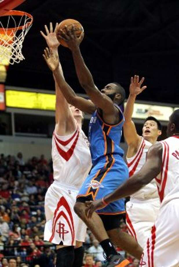 Oklahoma City Thunder's James Harden, center, goes to the basket past Houston Rockets' Omar Asik, left, and Jeremy Lin during the second quarter of an NBA preseason basketball game in Hidalgo, Texas, Wednesday, Oct. 10, 2012. (AP Photo/Delcia Lopez) (Associated Press)