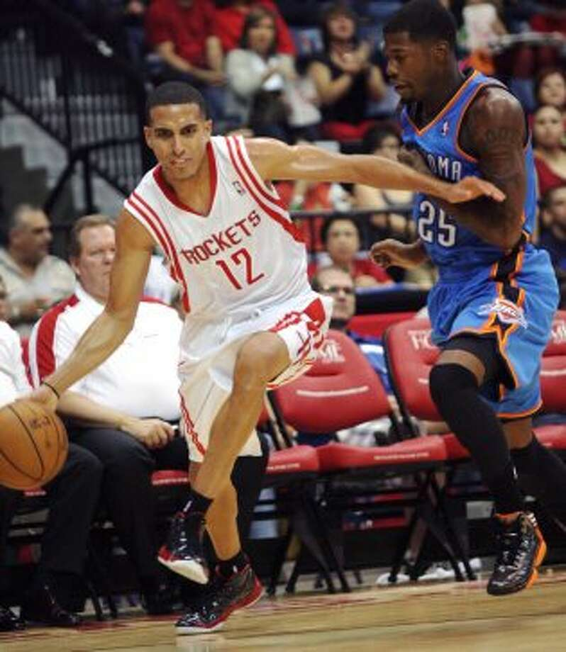 Houston Rockets' Kevin Martingets (12) dribbles past Oklahoma City Thunder's DeAndre Liggins during the second quarter of an NBA preseason basketball game in Hidalgo, Texas, Wednesday, Oct. 10, 2012. (AP Photo/Delcia Lopez) (Associated Press)
