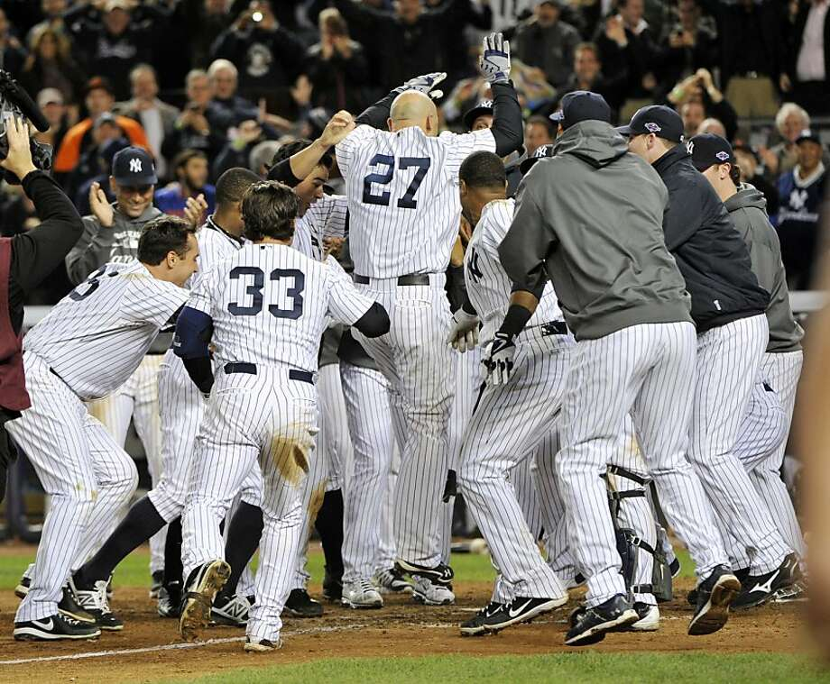 Raul Ibañez, who tied the game with a home run in the ninth, gets mobbed after winning it in the 12th. Photo: Bill Kostroun, Associated Press