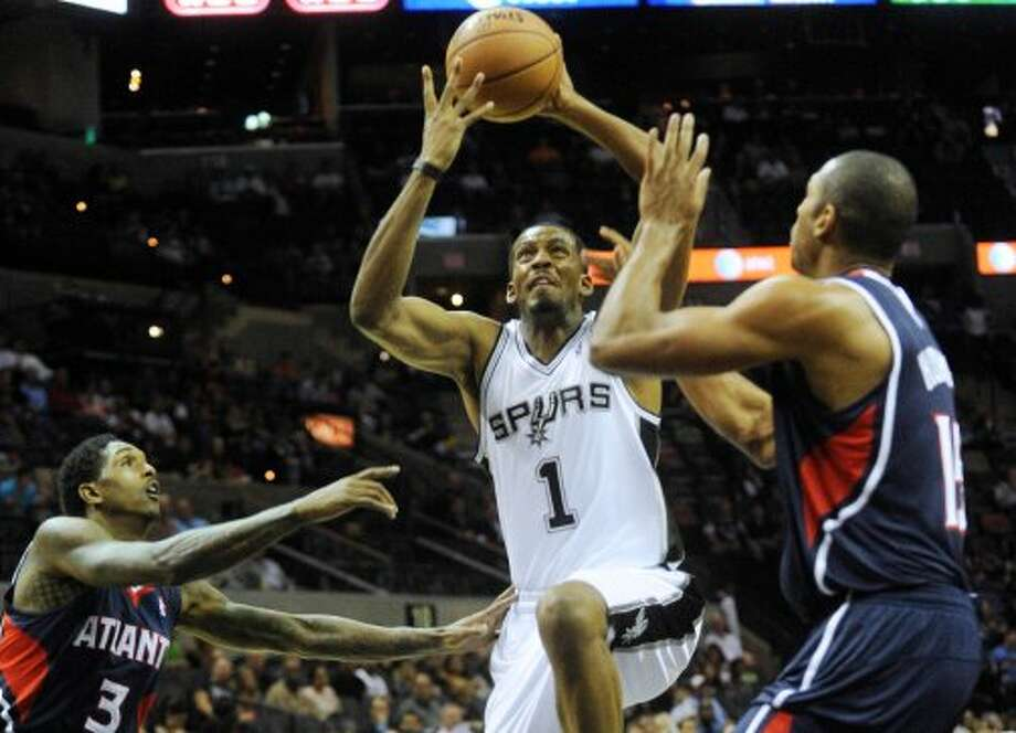 Derrick Brown of the Spurs (1) drives as Louis Williams, left, and Al Horford of Atlanta defend during preseason NBA action at the AT&T Center on Wednesday, Oct. 10, 2012. (Billy Calzada / San Antonio Express-News)