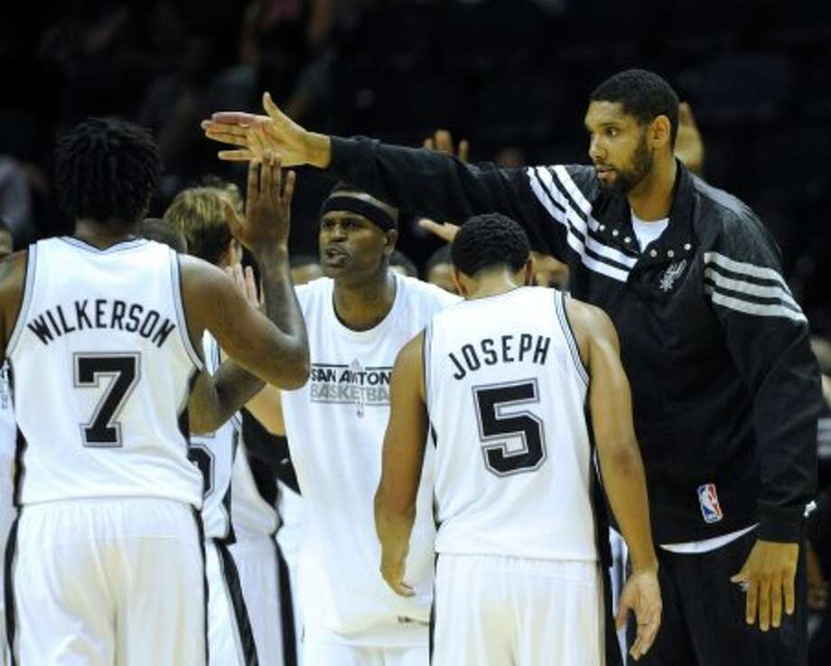 Tinm Duncan, right, encourages teammates Tyler Wilkerson (7) and Cory Joseph (5) during preseason NBA action at the AT&T Center against Atlanta on Wednesday, Oct. 10, 2012. (Billy Calzada / San Antonio Express-News)