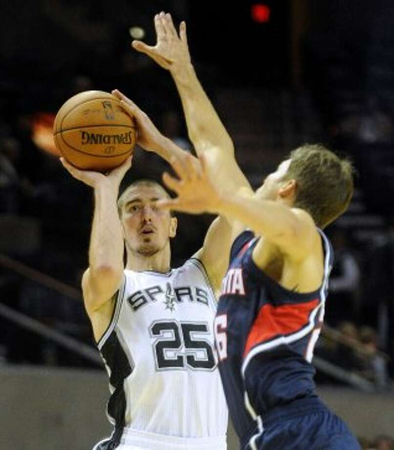 Nando de Colo of the Spurs shoots over Kyle Korver of Atlanta during first-half preseason NBA action at the AT&T Center on Wednesday, Oct. 10, 2012. (Billy Calzada / San Antonio Express-News)