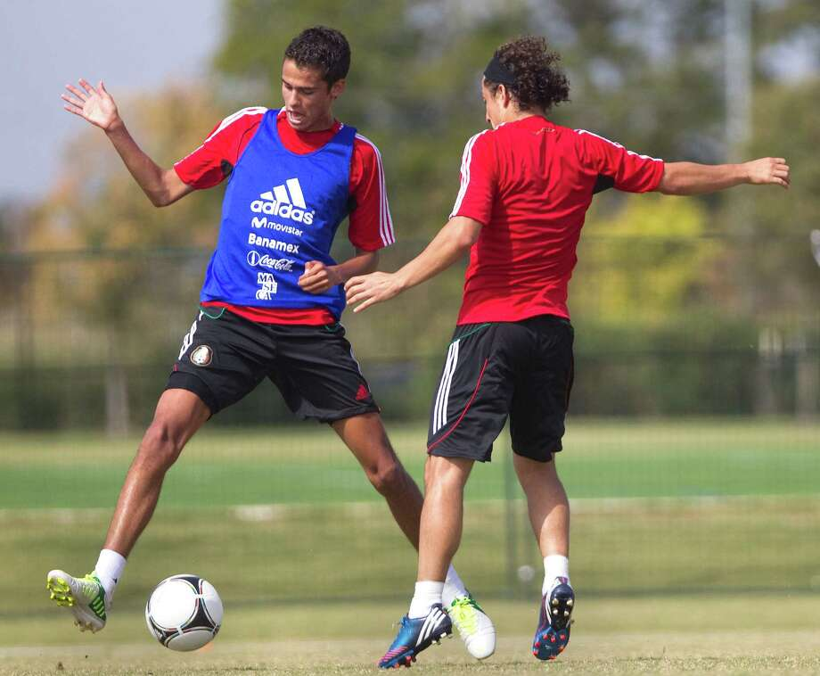 Mexico's Diego Reyes, left, dribbles past teammate Andres Guardado, right, during practice Tuesday. Photo: Cody Duty / © 2012 Houston Chronicle