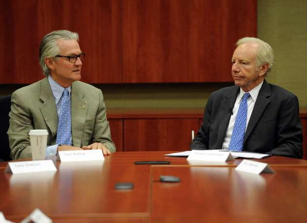 "Senator Joseph Lieberman, right, and Curt Welling, President and CEO of AmeriCares, left, speaks at AmeriCares in Stamford on Wednesday, October 10, 2012, where Lieberman presented the organization with a ""Joe's Hero"" award. Photo: Lindsay Niegelberg / Stamford Advocate"